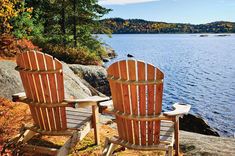 Two Muskoka chairs overlooking a lake
