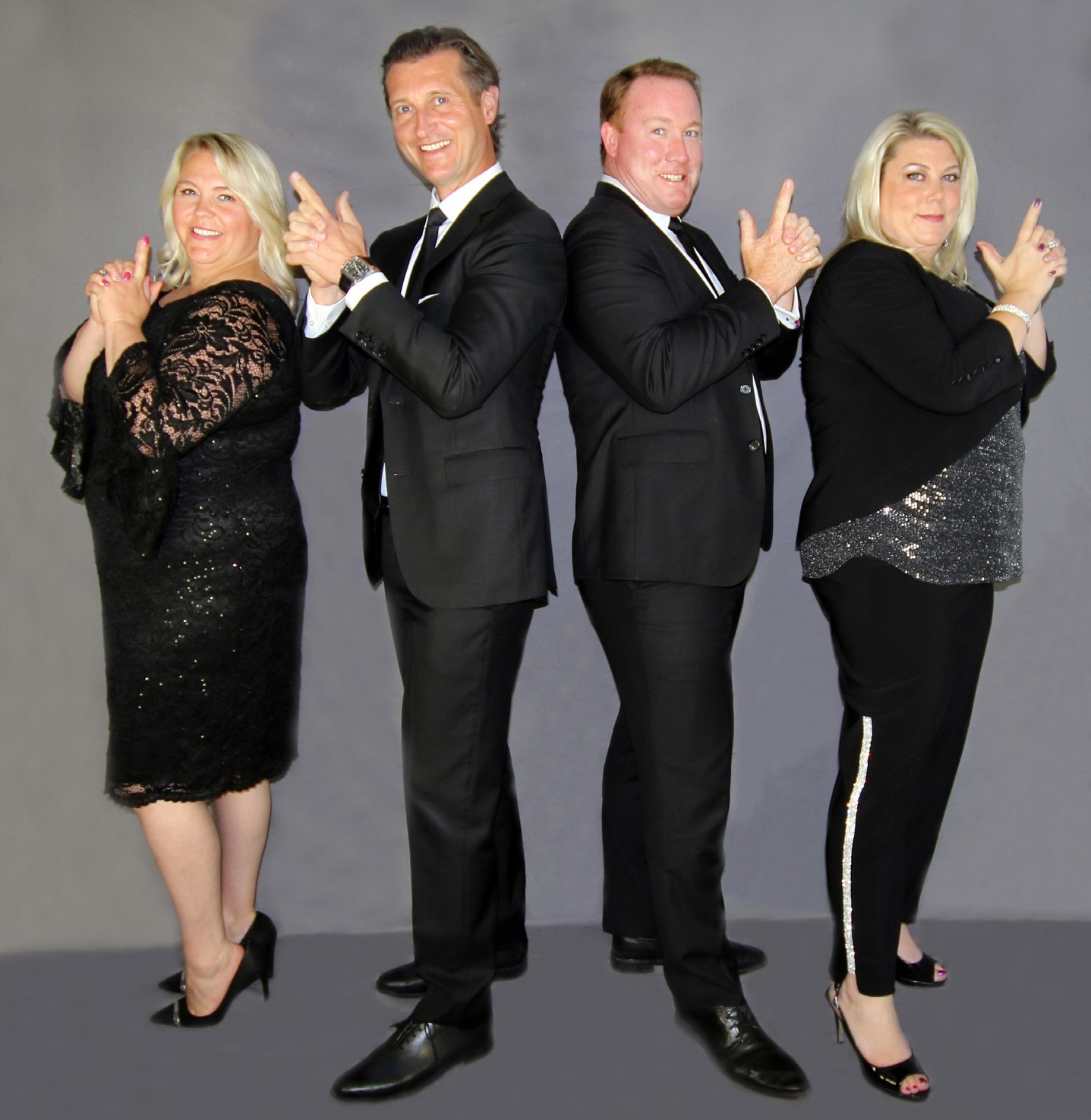Four people in formal dress in front of a grey background