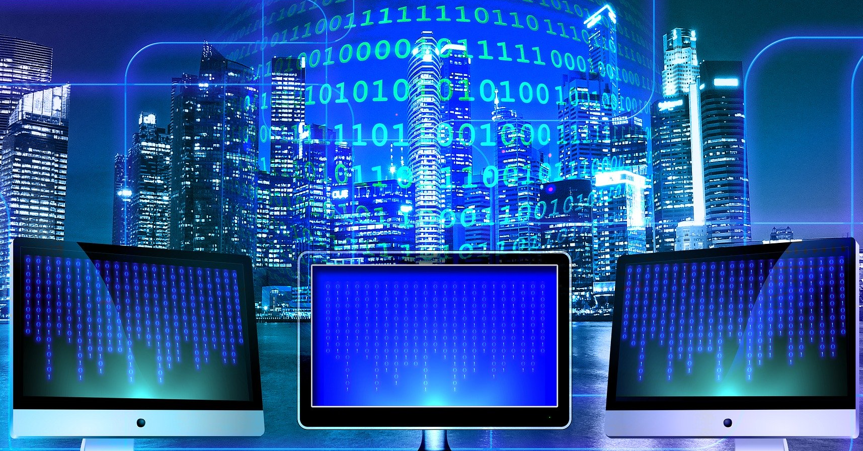 Computer monitors in front of a large city skyline, with overlayed with binary code.