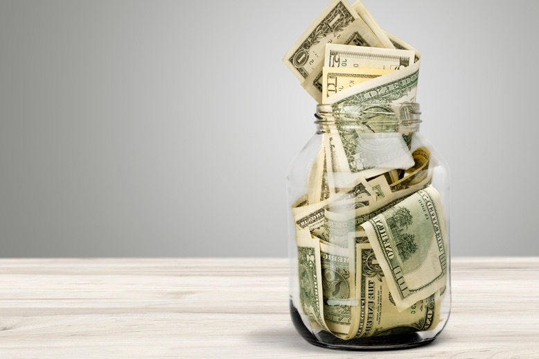 Bundle of money stuffed in a glass jar