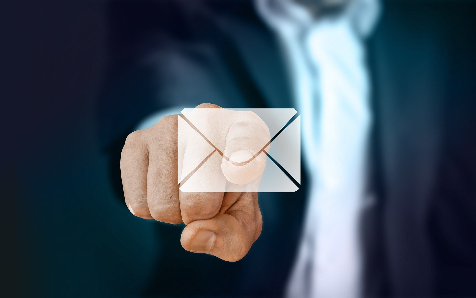 Man in a suit pointing at a white envelope