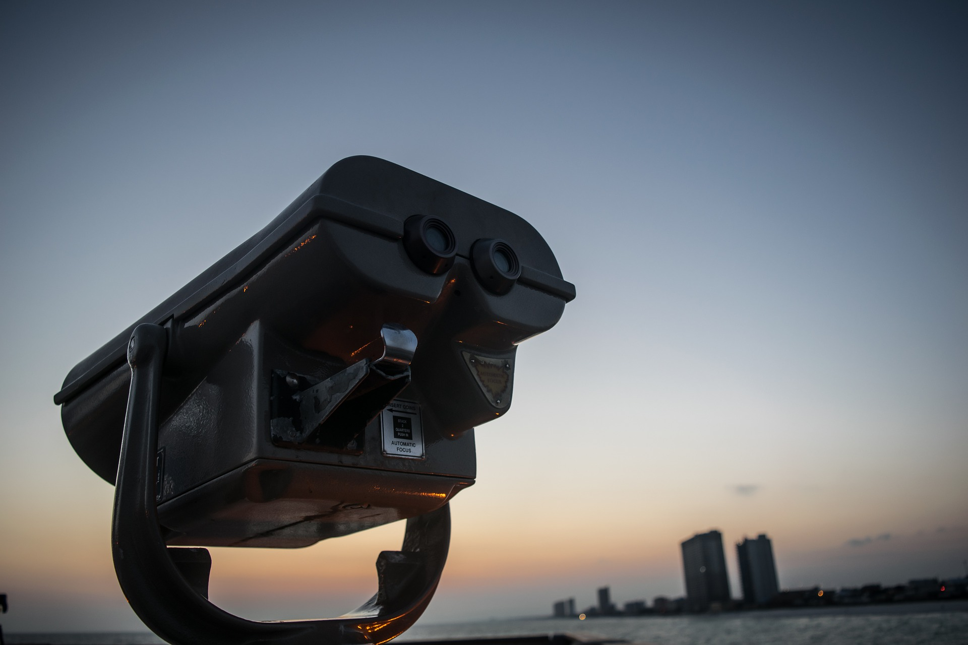 Coin operated binoculars overlooking water and city at dusk
