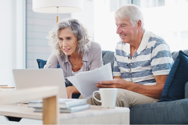 senior-couple-going-through-paperwork-on-sofa-at-home-in-page