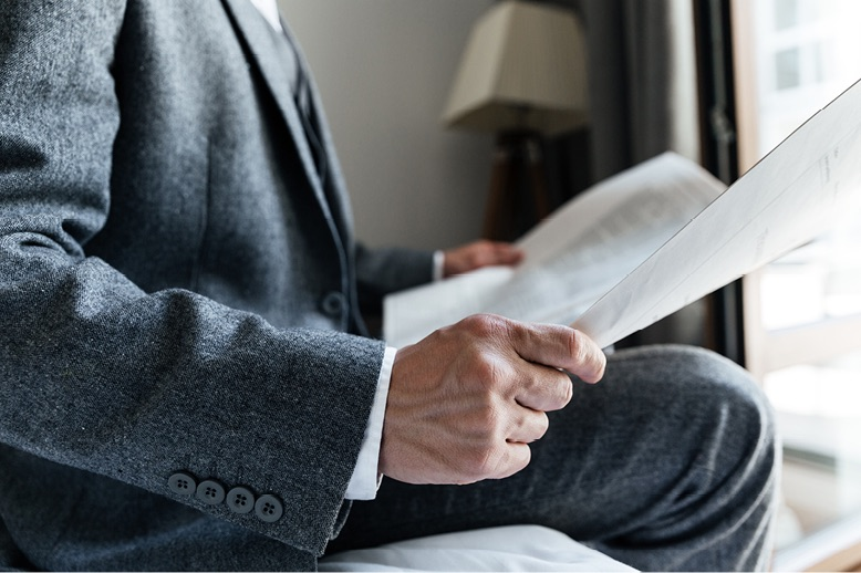 man in suit sitting reading paper