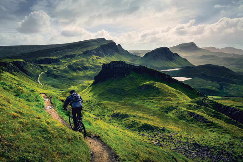 mountain-biker-on-long-green-trail-with-cloudy-sky-in-page