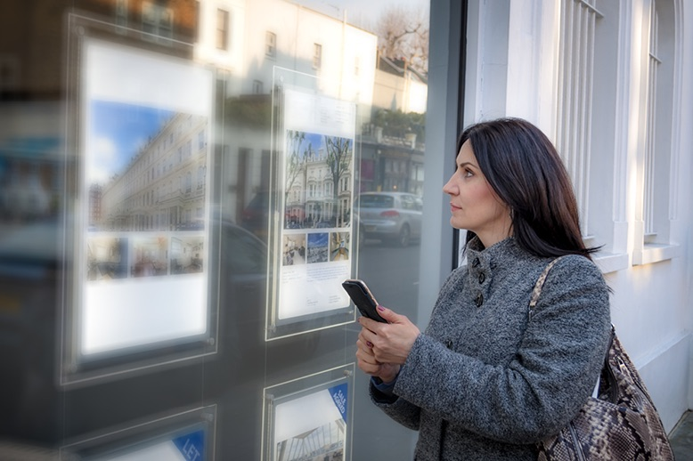 woman-looking-at-ads-in-real-estate-office-window-in-page