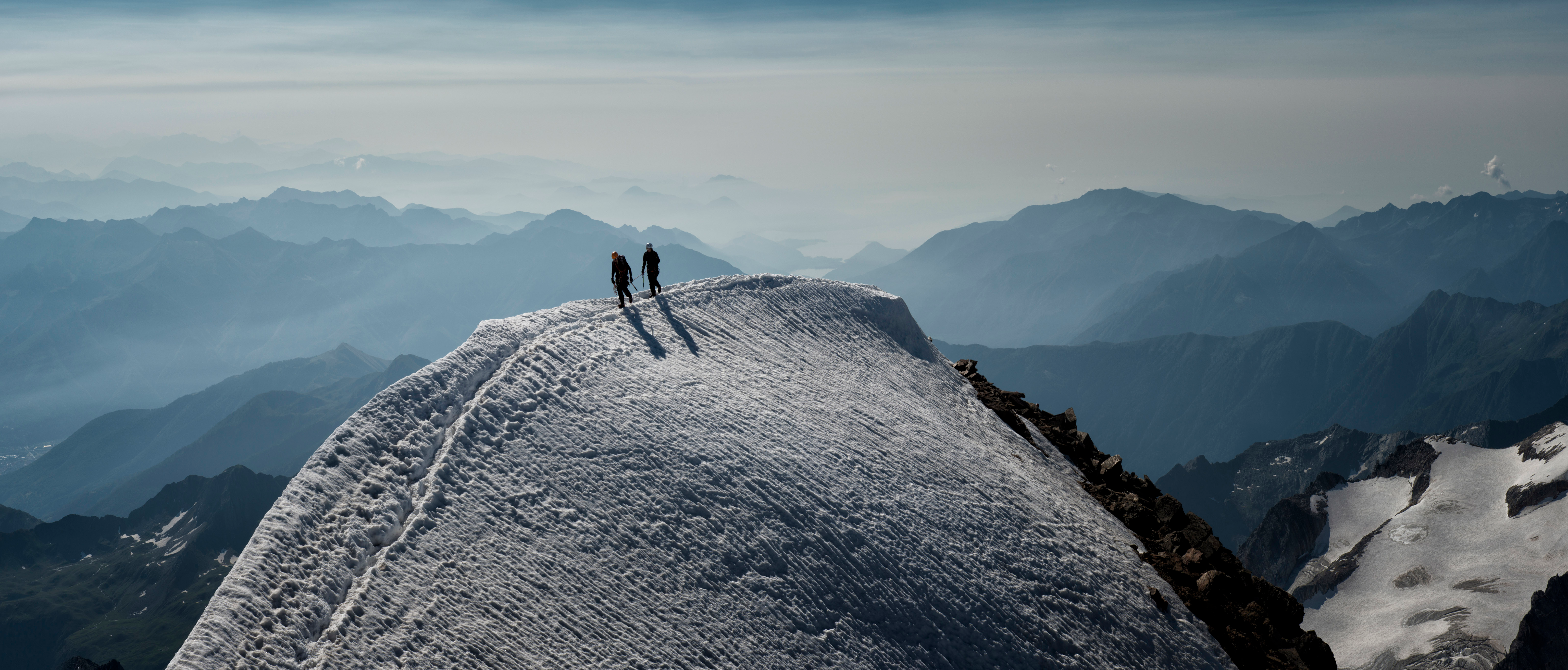 Two people at the crest of a snowy mountain.