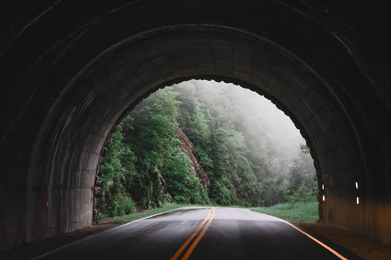 tunnel-roadway-through-foggy-green-mountain-terrain