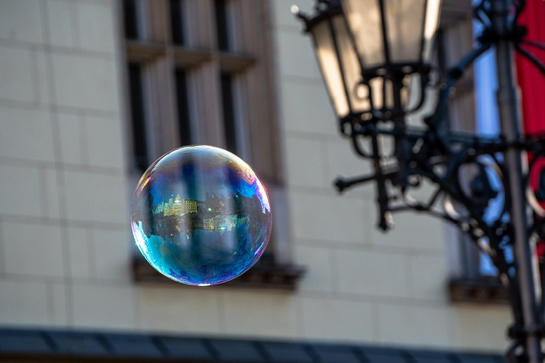 close up of soap bubble floating past historic building
