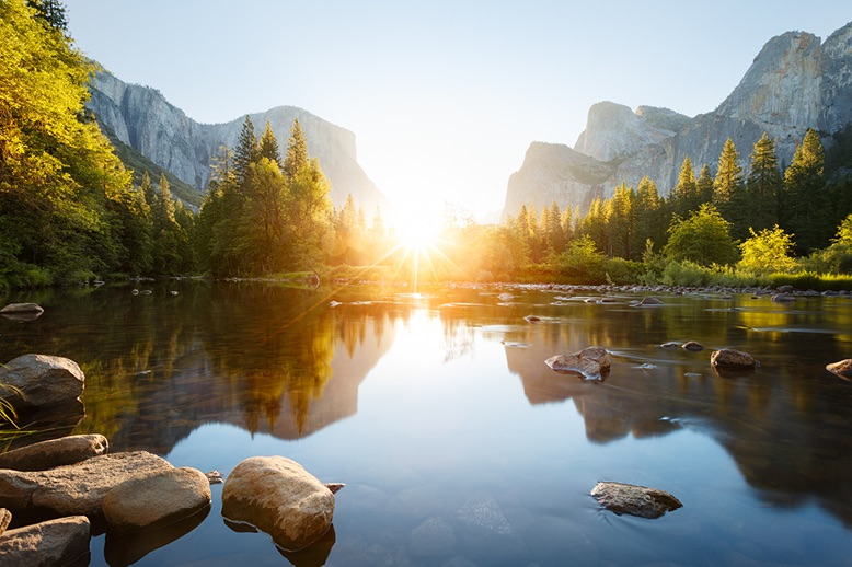 sun-rising-on-still-lake-in-yosemite-valley-in-page