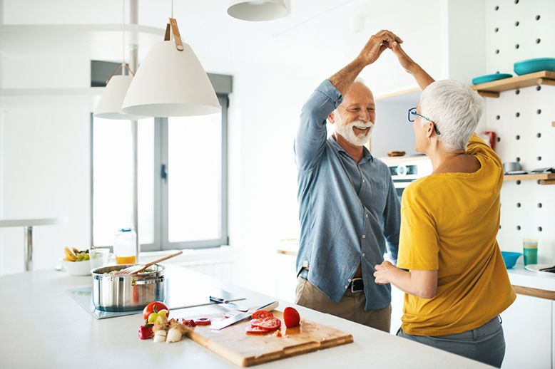 mature-couple-dancing-in-kitchen-while-cooking-in-page