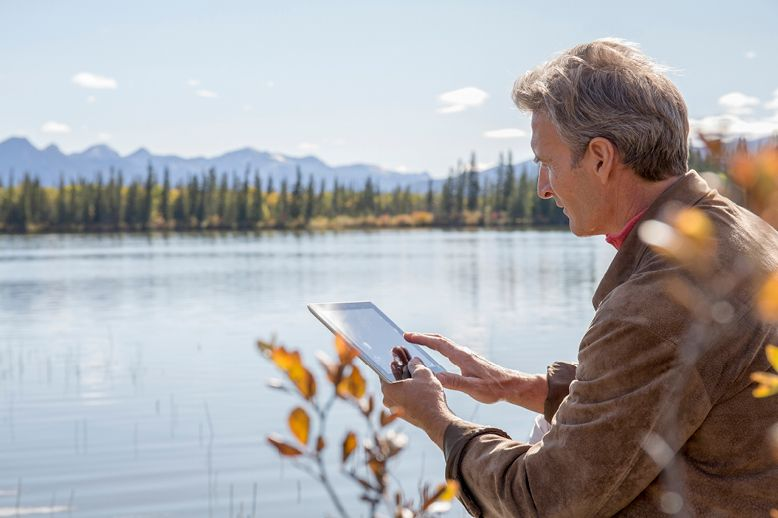 man-using-tablet-relaxing-by-alpine-lake-in-page