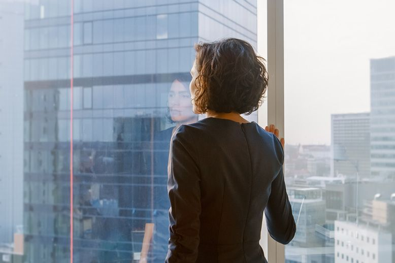 woman-looking-out-of-a-skyscraper-window-deep-in-thought-in-page