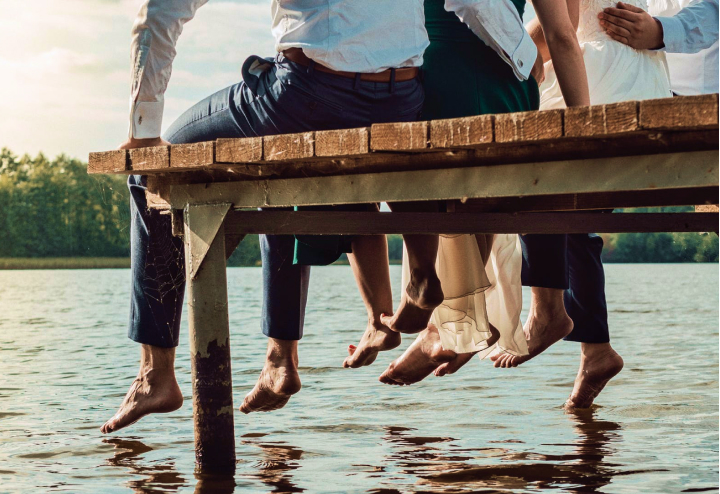 A family enjoys peace of a lake, sitting at the end of a dock with their feet in the water