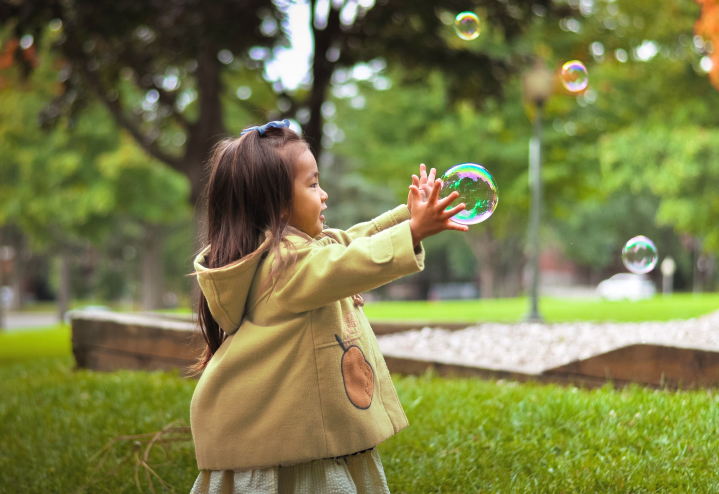 A little girl chases bubbles
