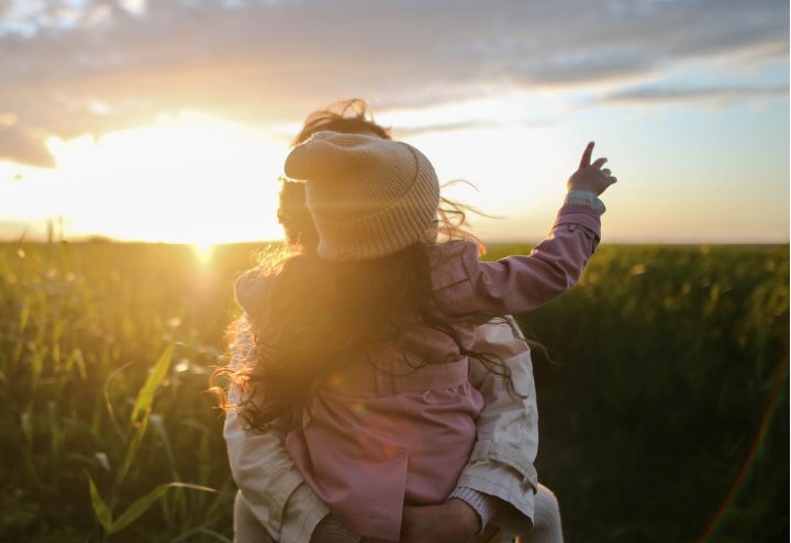 A mother holds her daughter in a field as the sun dips below the treeline, the little girl points to something in the distance.